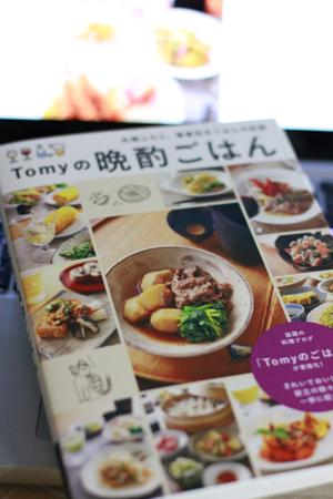 『Tomyの晩酌ごはん』レシピ本と、その背後にぼんやり写っているのは、『Tomyのごはん』ブログの画面